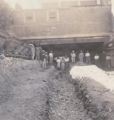 Trabajadores con palas y contenedores bajo el puente Benito Juárez, retrato de grupo
