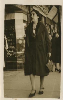 Mujer camina en una calle junto a una joyería, retrato