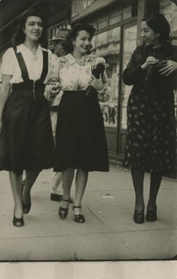 Tres mujeres se ríen mientras caminan por una calle, tarjeta postal