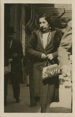 Mujer camina por una calle, viste un abrigo, tarjeta postal