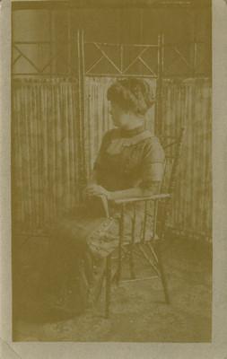 Mujer sentada de perfil izquierdo, tiene un libro sobre su regazo, retrato