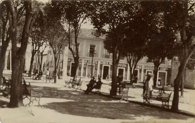 Vista de comercios en una plaza pública, tarjeta postal