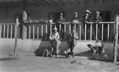 Hombres con perros posan en el pórtico de una casa, retrato de grupo