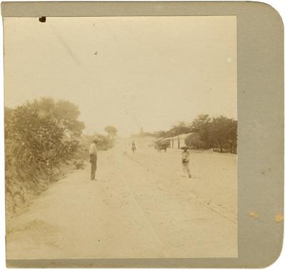 Personas en medio de una calle a la entrada de un poblado
