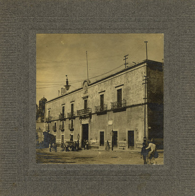 """Personas caminan frente a la """"Casa del corregidor [Miguel] Domínguez"""""""
