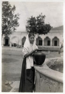 Adolescente indígena junto a una fuente con una olla