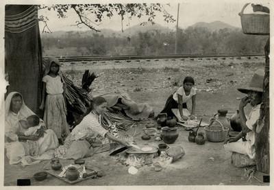 Familia junto a la vía del tren preparan alimentos al aire libre