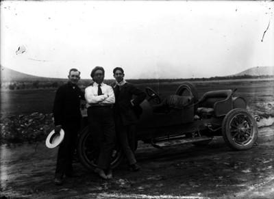 Amaury Muñoz, corredor de autos, en compañía de dos hombres recargados de un automóvil, retrato