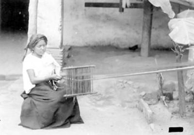 Mujer trabaja con un telar