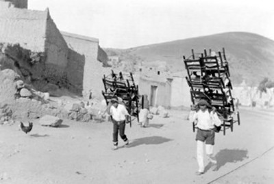 Vendedores de sillas; llevan su mercancia a cuestas en la espalda