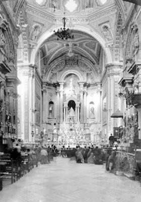 Feligreses en misa, al fondo el altar mayor
