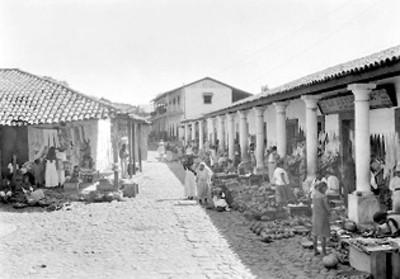 Vendedores ambulantes con sus mercancías en los portales de un pueblo