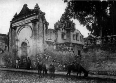 Hombres y niños observan a asnos comer afuera de la iglesia del Santo Ángel Custodio de Analco