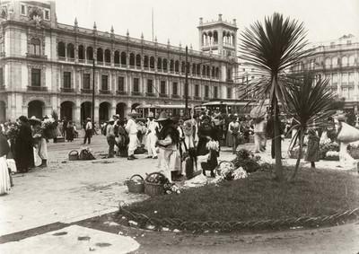 Venderores de flores en el zócalo de la Ciudad de México, frente al Palacio del Ayuntamiento