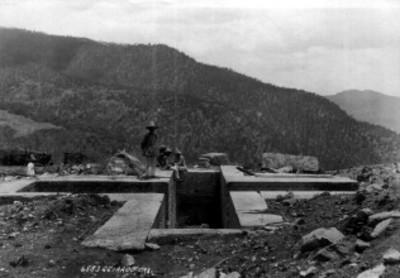 Indígenas sentados en los bordes de una tumba cruciforme