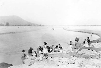 Mujeres con niños se bañan en un río
