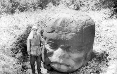Hombre toca con la amno una cabeza colosal Olmeca