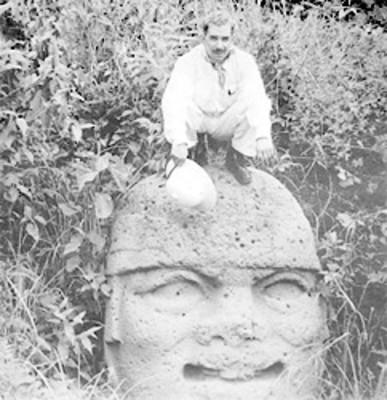 Hombre en cuclillas arriba de una cabeza colosal olmeca