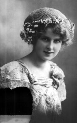 Mujer sonríe y posa con red en la cabeza y vestido, retrato