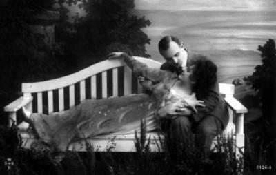 Mujer recostada es abrazada por hombre en una banca de parque