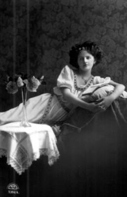 Mujer joven recostada sobre sillón junto a mesa con mantel y florero