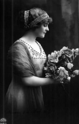 Mujer de perfil posa con vestido y adornos en el cabello, toma un racimo de flores entre sus manos