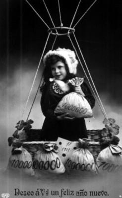 Niña sonríe sobre canastilla de globo aerostático y sujeta un saco con sus manos
