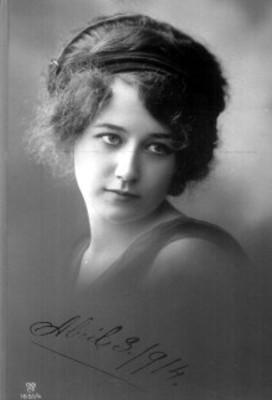 Mujer mira hacia la izquierda, lleva el cabello recogido, retrato
