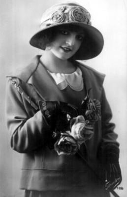 Mujer sonríe, posa con sombrero y guantes, retrato