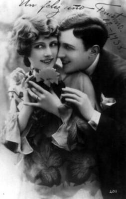 Hombre sonríe y coloca su rostro sobre el hombro de una mujer
