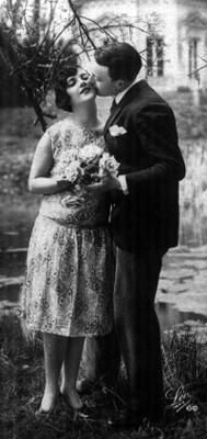Hombre besa la mejilla de una mujer, ambos posan de pie en un jardín