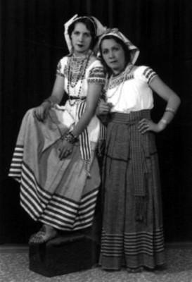 Par de mujeres con trajes folclóricos posan de pie, retrato