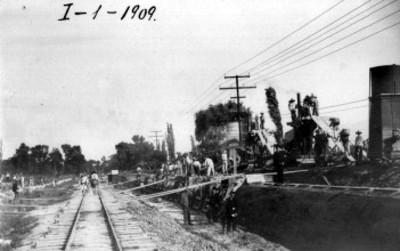 Hombres trabajan en obra junto a vías ferroviarias