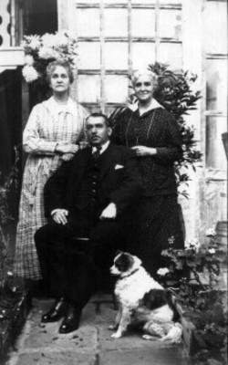 Hombre sentado posa junto a dos mujeres de pie y un perro en jardín