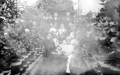 Tarjeta postal con el retrato de una familia ubicada en un jardín