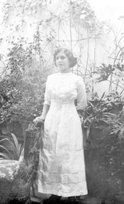 Mujer de pie junto a una silla entre plantas