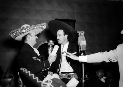 Jorge Negrete, cantante recibiendo un obsequio de un hombre vestido de charro ante los micrófonos de la XEW