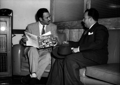 Jorge Negrete, actor y cantante dialogando con un hombre en una sala