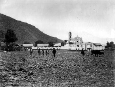 Campesinos en campo de cultivo junto a la iglesia