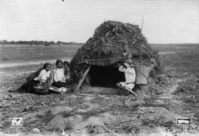 Indígenas afuera de su vivienda