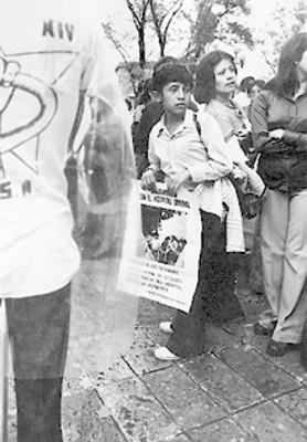 Adolescente con cartel entre manifestantes del Hospital General