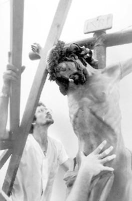 Hombres frente a crucifijo