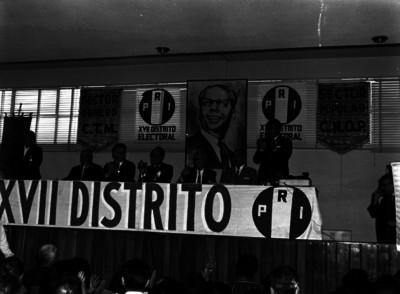 Raúl Noriega en presídium saludando, mientras es apludido por los asistentes a una asamblea del PRI, en un auditorio