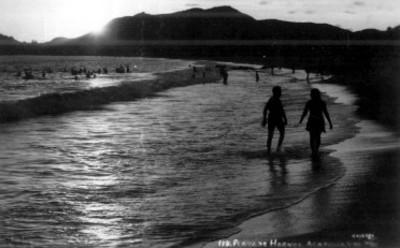 Tarjeta postal con imagen de gente en la playa durante el atardecer