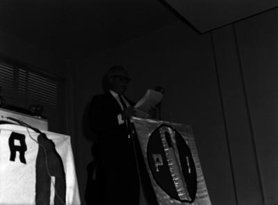 Raúl Noriega dando lectura a un discurso, durante una asamblea del PRI, en un auditorio