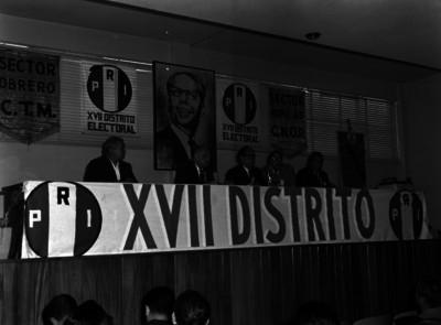 Funcionarios públicos en presídium, durante una asamblea del XVII Distrito electoral del PRI, en un auditorio