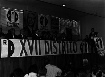 Raúl Noriega y funcionarios en presídium, ante el discurso de un hombre, durante una asamblea del XVII Distrito electoral del PRI