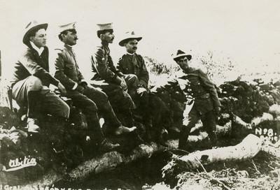 Obregón en compañía de jefes militares en un muro de piedras, retrato de grupo