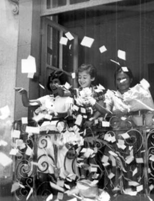 Niñas arrojan papelitos desde un balcón