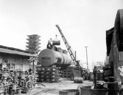 Obreros cargan carro tanque en patios de instalación industrial